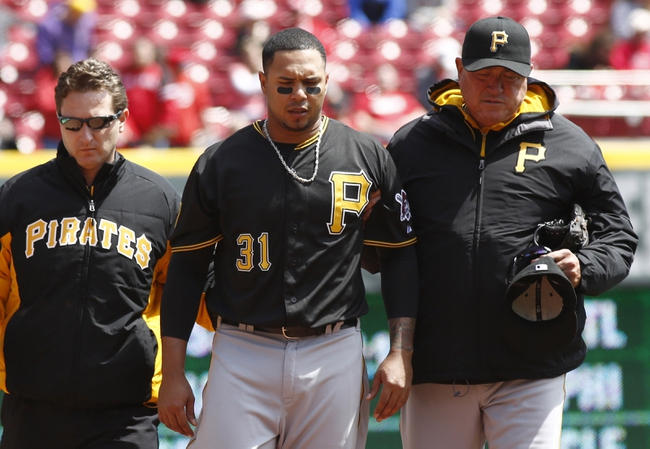 Apr 16, 2014; Cincinnati, OH, USA; Pittsburgh Pirates left fielder Jose Tabata (31) is walked off the field by manager Clint Hurdle, right, and  head trainer Todd Tomczyk, left, after Tabata hit the left field wall on a fly ball from Cincinnati Reds catcher Brayan Pena during the fifth inning at Great American Ball Park. The Reds won 4-0. Mandatory Credit: David Kohl-USA TODAY Sports