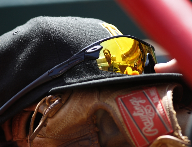 Apr 16, 2014; Cincinnati, OH, USA; Pittsburgh Pirates shortstop Jordy Mercer, pictured in glasses, reaches for his hat and glove during a game against the Cincinnati Reds at Great American Ball Park. The Reds won 4-0. Mandatory Credit: David Kohl-USA TODAY Sports