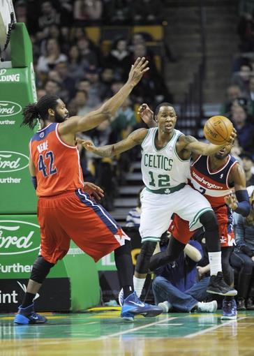 Apr 16, 2014; Boston, MA, USA; Boston Celtics forward Chris Johnson (12) grabs a rebound while Washington Wizards forward Nene Hilario (42) defends during the first half at TD Garden. Mandatory Credit: Bob DeChiara-USA TODAY Sports