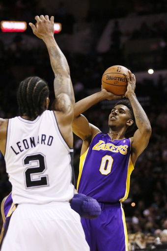Apr 16, 2014; San Antonio, TX, USA; Los Angeles Lakers forward Nick Young (0) shoots the ball over San Antonio Spurs forward Kawhi Leonard (2) during the first half at AT&T Center. Mandatory Credit: Soobum Im-USA TODAY Sports
