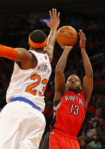 Apr 16, 2014; New York, NY, USA;  Toronto Raptors guard Dwight Buycks (13) gets off a jump shot against New York Knicks guard Toure' Murry (23) during the first half at Madison Square Garden. Mandatory Credit: Jim O'Connor-USA TODAY Sports
