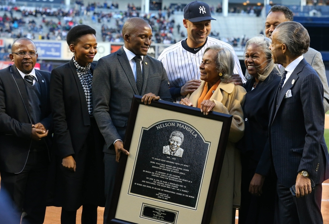 Apr 16, 2014; Bronx, NY, USA; New York Yankees shortstop Derek Jeter (2) poses with the replica plaque with Zondwa Mandela, Rachel Robinson, and Sharon Robinson during the Jackie Robinson ceremonies as the New York Yankees take on the Chicago Cubs in 2nd game of the day/night double header at Yankee Stadium. Mandatory Credit: Anthony Gruppuso-USA TODAY Sports