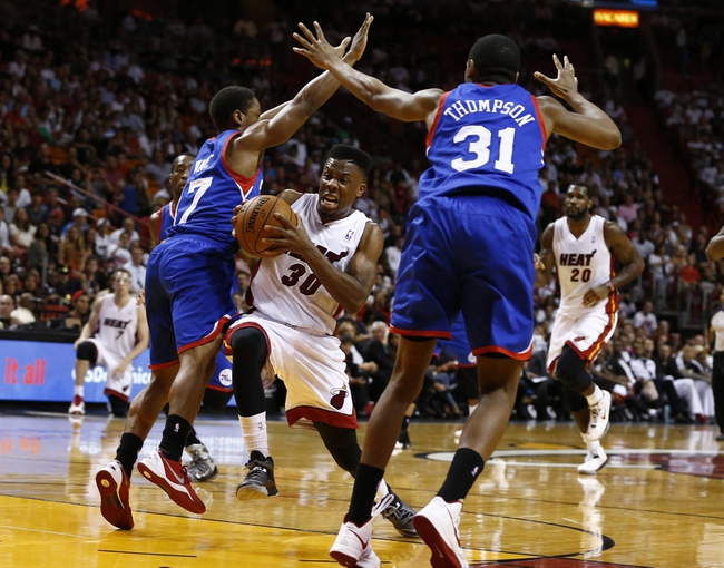 Apr 16, 2014; Miami, FL, USA; Miami Heat guard Norris Cole (30) drives to the basket between Philadelphia 76ers guard Hollis Thompson (31) and guard Casper Ware (17) in the second half at American Airlines Arena. The 76ers won 100-87. Mandatory Credit: Robert Mayer-USA TODAY Sports