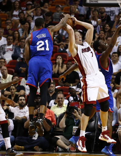 Apr 16, 2014; Miami, FL, USA; Philadelphia 76ers forward Thaddeus Young (21) and Miami Heat center Justin Hamilton (7) battle for a rebound in the second half at American Airlines Arena. The 76ers won 100-87. Mandatory Credit: Robert Mayer-USA TODAY Sports