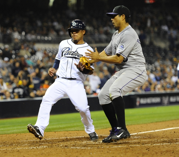 Apr 16, 2014; San Diego, CA, USA; San Diego Padres third baseman Alexi Amarista (5) scores while trying to avoid contact with Colorado Rockies starting pitcher Jorge De La Rosa (29) during the fifth inning at Petco Park. Mandatory Credit: Christopher Hanewinckel-USA TODAY Sports