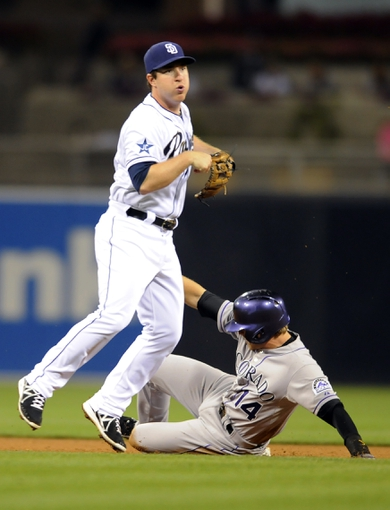 Apr 16, 2014; San Diego, CA, USA; San Diego Padres second baseman Jedd Gyorko (9) turns a double play ahead of the slide by Colorado Rockies second baseman Josh Rutledge (14) during the sixth inning at Petco Park. Mandatory Credit: Christopher Hanewinckel-USA TODAY Sports