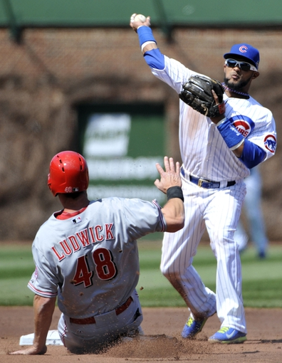 Apr 18, 2014; Chicago, IL, USA;  Chicago Cubs second baseman Emilio Bonifacio (64) forces out Cincinnati Reds left fielder Ryan Lud