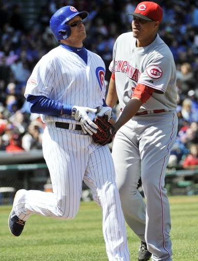 Apr 18, 2014; Chicago, IL, USA; Cincinnati Reds starting pitcher Alfredo Simon (31) tags out Chicago Cubs center fielder Ryan Sweeney (6) during the second inning at Wrigley Field. Mandatory Credit: David Banks-USA TODAY Sports