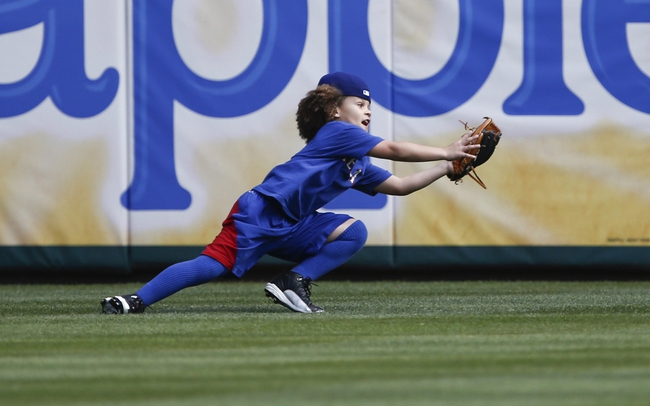 Apr 18, 2014; Arlington, TX, USA; Jaden Fielder (left), the son of Texas Rangers first baseman Prince Fielder (not pictured) catches a fly ball during batting practice before the baseball game between the Texas Rangers and the Chicago White Sox at Rangers Ballpark in Arlington. Mandatory Credit: Jim Cowsert-USA TODAY Sports
