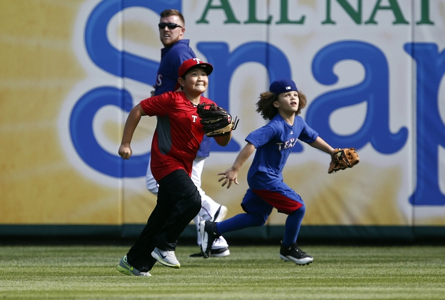 Apr 18, 2014; Arlington, TX, USA; Jaden Fielder (left), the son of Prince Fielder (not pictured) and Alan Choo, the son of Shin-Soo Choo (not pictured) chase fly balls during batting practice before the baseball game between the Texas Rangers and the Chicago White Sox at Rangers Ballpark in Arlington. Mandatory Credit: Jim Cowsert-USA TODAY Sports