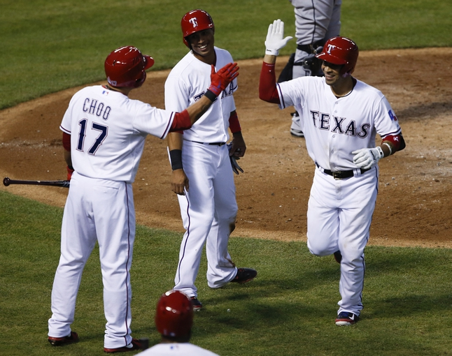 Apr 18, 2014; Arlington, TX, USA; Texas Rangers catcher Robinson Chirinos (61) celebrates with left fielder Shin-Soo Choo (17) and center fielder Leonys Martin (2) after hitting a two run homer against the Chicago White Sox during the third inning of a baseball game at Rangers Ballpark in Arlington. Mandatory Credit: Jim Cowsert-USA TODAY Sports