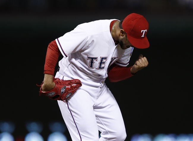 Apr 18, 2014; Arlington, TX, USA; Texas Rangers starting pitcher Martin Perez (33) celebrates after defeating the Chicago White Sox 12-0 at Rangers Ballpark in Arlington. Mandatory Credit: Jim Cowsert-USA TODAY Sports