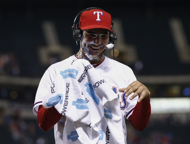 Apr 18, 2014; Arlington, TX, USA; Texas Rangers starting pitcher Martin Perez (33) wipes his face after getting a shaving cream pie after defeating the Chicago White Sox 12-0 at Rangers Ballpark in Arlington. Mandatory Credit: Jim Cowsert-USA TODAY Sports