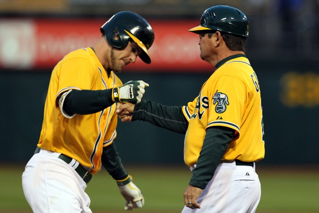 Apr 18, 2014; Oakland, CA, USA; Oakland Athletics right fielder Josh Reddick (16) is greeted by third base coach Mike Gallego (2) after hitting a two run home run against the Houston Astros in the first inning of their baseball game at O.co Coliseum. Mandatory Credit: Lance Iversen-USA TODAY Sports