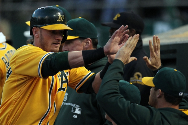 Apr 18, 2014; Oakland, CA, USA; Oakland Athletics third baseman Josh Donaldson (20) celebrates with teammates after scoring against the Houston Astros in the first inning of their baseball game at O.co Coliseum. Mandatory Credit: Lance Iversen-USA TODAY Sports