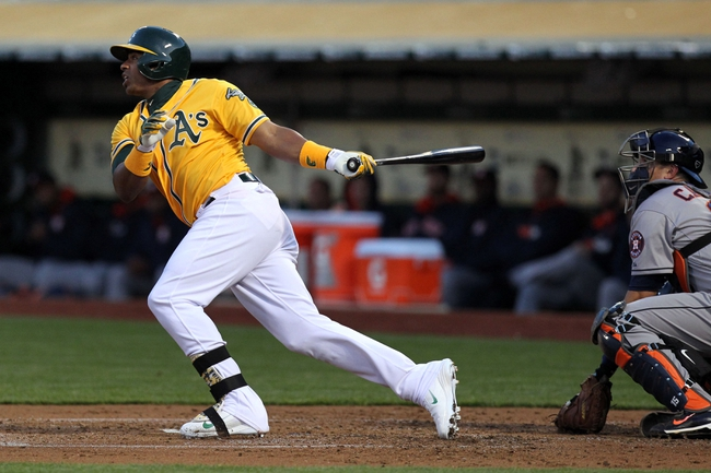 Apr 18, 2014; Oakland, CA, USA; Oakland Athletics Yoenis Cespedes (52) hits a two run RBI against the Houston Astros in the first inning of their baseball game at O.co Coliseum. Mandatory Credit: Lance Iversen-USA TODAY Sports