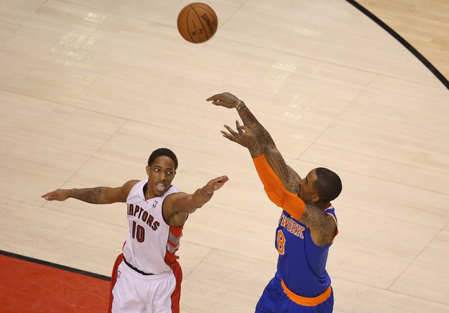 Apr 11, 2014; Toronto, Ontario, CAN; New York Knicks forward J.R. Smith (8) hits a shot against the defense of Toronto Raptors guard DeMar DeRozan (10) at Air Canada Centre. The Knicks beat the Raptors 108-100. Mandatory Credit: Tom Szczerbowski-USA TODAY Sports