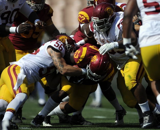 Apr 19, 2014; Los Angeles, CA, USA; Southern California tailback Tre Madden (center) moves the ball tackled by Southern California inside linebacker Anthony Sarao (left) and defensive lineman Antwaun Woods (right) during the Southern California Spring Game at Los Angeles Memorial Coliseum. Mandatory Credit: Kelvin Kuo-USA TODAY Sports