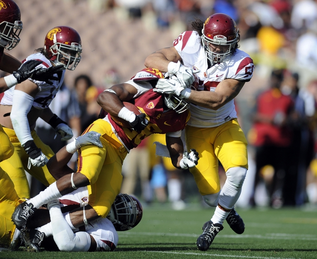 Apr 19, 2014; Los Angeles, CA, USA; Southern California inside linebacker Anthony Sarao (56) tackles Southern California tailback James Toland (26) during the Southern California Spring Game at Los Angeles Memorial Coliseum. Mandatory Credit: Kelvin Kuo-USA TODAY Sports