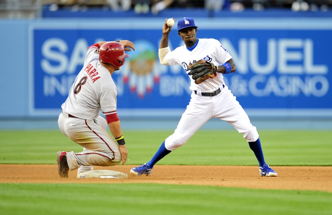 April 19, 2014; Los Angeles, CA, USA; Los Angeles Dodgers second baseman Dee Gordon (9) throws to first turning a double play as Arizona Diamondbacks right fielder Gerardo Parra (8) slides into second in the fifth inning at Dodger Stadium. Mandatory Credit: Gary Vasquez-USA TODAY Sports