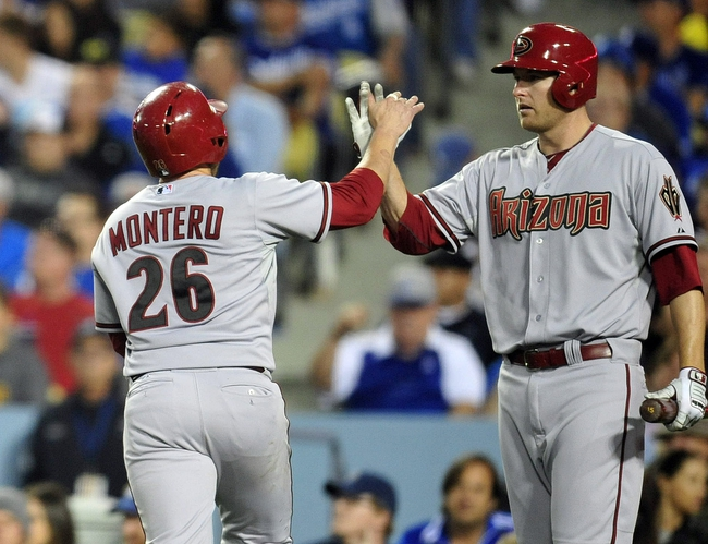 April 19, 2014; Los Angeles, CA, USA; Arizona Diamondbacks catcher Miguel Montero (26) is greeted at home plate by left fielder Mark Trumbo (15) after scoring a run in the eighth inning against the Los Angeles Dodgers at Dodger Stadium. Mandatory Credit: Gary Vasquez-USA TODAY Sports