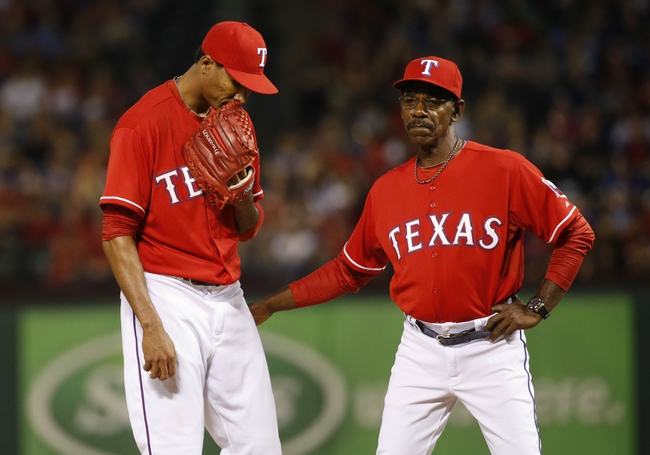 Apr 19, 2014; Arlington, TX, USA; Texas Rangers manager Ron Washington (38) speaks with relief pitcher Alexi Ogando (41) during the game against the Chicago White Sox at Globe Life Park in Arlington. Texas won 6-3. Mandatory Credit: Kevin Jairaj-USA TODAY Sports