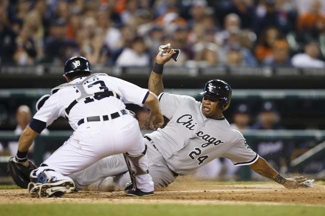 Apr 21, 2014; Detroit, MI, USA; Chicago White Sox right fielder Dayan Viciedo (24) slides into home plate as Detroit Tigers catcher Alex Avila (13) raises his glove in the seventh inning at Comerica Park. Viciedo was called out but the play was overturned after being reviewed. Mandatory Credit: Rick Osentoski-USA TODAY Sports