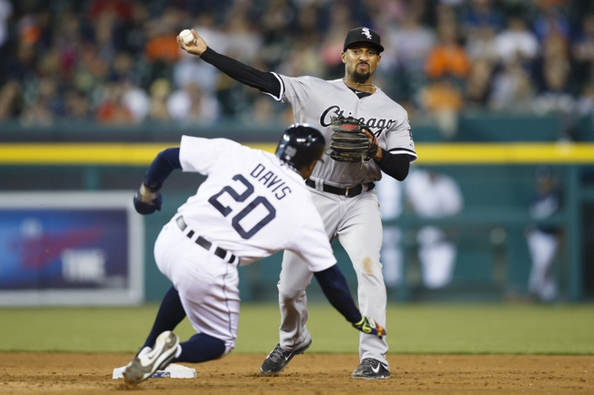 Apr 21, 2014; Detroit, MI, USA; Chicago White Sox second baseman Marcus Semien (5) makes a throw to first to complete a double play as Detroit Tigers left fielder Rajai Davis (20) slides into second in the seventh inning at Comerica Park. Mandatory Credit: Rick Osentoski-USA TODAY Sports