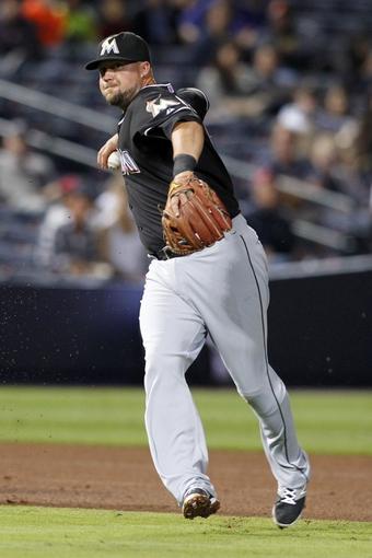 Apr 22, 2014; Atlanta, GA, USA; Miami Marlins third baseman Casey McGehee (9) throws a runner out at first against the Atlanta Braves in the sixth inning at Turner Field. Mandatory Credit: Brett Davis-USA TODAY Sports