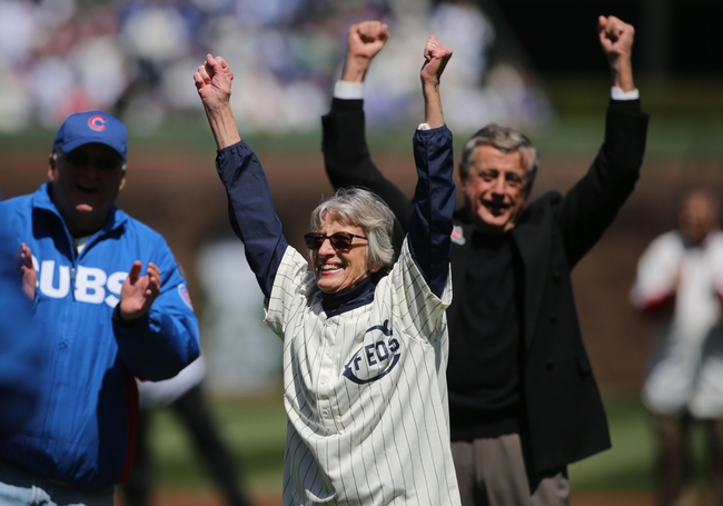 Apr 23, 2014; Chicago, IL, USA; Sue Quigg a representative from the Weeghman family celebrates after throwing out the ceremonial first pitch before the baseball game between the Chicago Cubs and Arizona Diamondbacks at Wrigley Field. Today marks the 100th year anniversary of the stadium's opening. Mandatory Credit: Jerry Lai-USA TODAY Sports