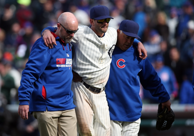 Apr 23, 2014; Chicago, IL, USA; Chicago Cubs outfielder Justin Ruggiano (middle) is helped off the field by manager Rick Renteria (right) and a trainer after sustaining an injury during the ninth inning of a baseball game against the Arizona Diamondbacks at Wrigley Field. Mandatory Credit: Jerry Lai-USA TODAY Sports