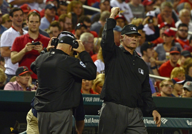 Apr 25, 2014; St. Louis, MO, USA; Third base umpire Ted Barrett (65) calls out St. Louis Cardinals center fielder Jon Jay (not pictured) after the original call was challenged by the Pittsburgh Pirates during the third inning at Busch Stadium. Mandatory Credit: Jeff Curry-USA TODAY Sports