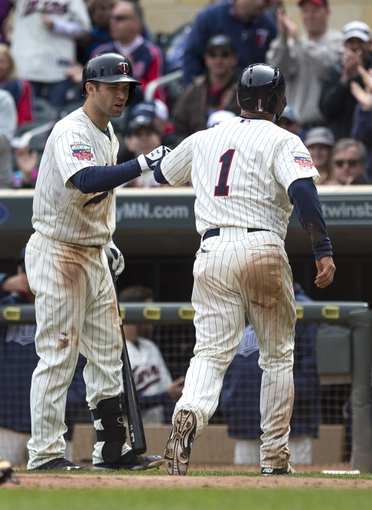 Apr 26, 2014; Minneapolis, MN, USA; Minnesota Twins right fielder Sam Fuld (1) celebrates with second baseman Brian Dozier (2) after scoring a run in the fifth inning against the Detroit Tigers at Target Field. Mandatory Credit: Jesse Johnson-USA TODAY Sports