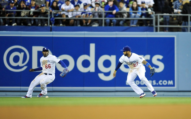 April 26, 2014; Los Angeles, CA, USA; Los Angeles Dodgers right fielder Yasiel Puig (66) and center fielder Matt Kemp (27) miss catching a fly ball in the fifth inning against the Colorado Rockies at Dodger Stadium. Mandatory Credit: Gary Vasquez-USA TODAY Sports