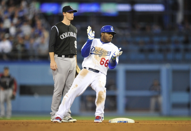 April 26, 2014; Los Angeles, CA, USA; Los Angeles Dodgers right fielder Yasiel Puig (66) advances to second in the fourth inning against the Colorado Rockies at Dodger Stadium. Mandatory Credit: Gary Vasquez-USA TODAY Sports