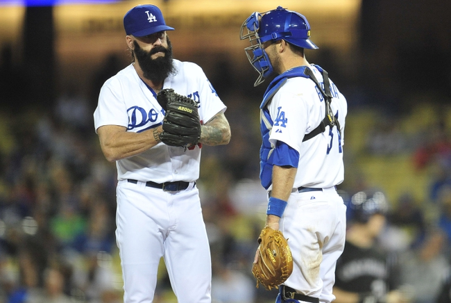 April 26, 2014; Los Angeles, CA, USA; Los Angeles Dodgers relief pitcher Brian Wilson (00) speaks with catcher Drew Butera (31) during the ninth inning at Dodger Stadium. Mandatory Credit: Gary Vasquez-USA TODAY Sports