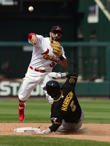 Apr 27, 2014; St. Louis, MO, USA; St. Louis Cardinals shortstop Daniel Descalso (33) completes the double play as Pittsburgh Pirates pinch hitter Josh Harrison (5) slides during the eighth inning at Busch Stadium. St. Louis defeated Pittsburgh 7-0. Mandatory Credit: Jeff Curry-USA TODAY Sports