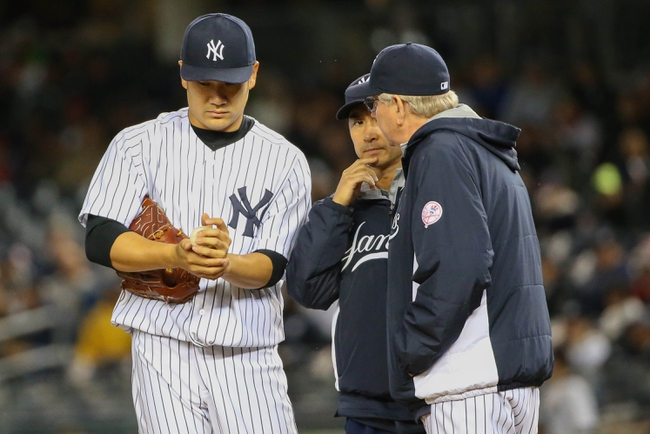 Apr 27, 2014; Bronx, NY, USA;  New York Yankees pitching coach Larry Rothschild (58) visits starting pitcher Masahiro Tanaka (19) during the fourth inning against the Los Angeles Angels at Yankee Stadium. Mandatory Credit: Anthony Gruppuso-USA TODAY Sports
