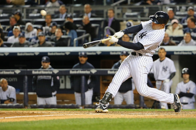 Apr 27, 2014; Bronx, NY, USA;  New York Yankees first baseman Mark Teixeira (25) hits a home run to right during the seventh inning against the Los Angeles Angels at Yankee Stadium. New York Yankees won 3-2.  Mandatory Credit: Anthony Gruppuso-USA TODAY Sports