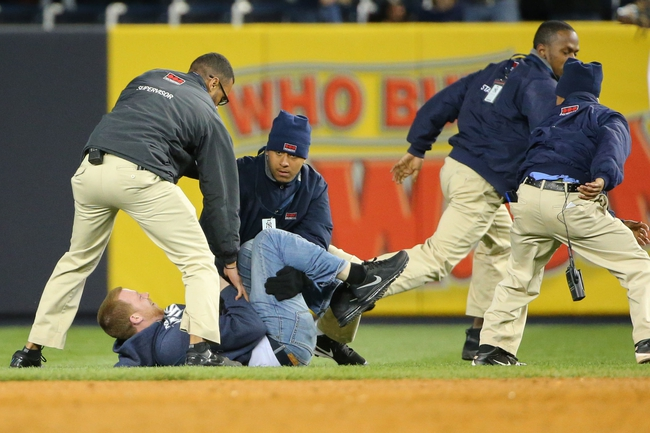 Apr 27, 2014; Bronx, NY, USA;  Security restrains a fan on the field after the game between the New York Yankees and the Los Angeles Angels at Yankee Stadium. New York Yankees won 3-2.  Mandatory Credit: Anthony Gruppuso-USA TODAY Sports