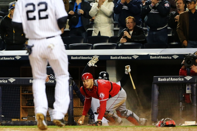 Apr 27, 2014; Bronx, NY, USA;  Los Angeles Angels catcher Chris Iannetta (17) climbs out of the New York Yankees dug out after retrieving a ball as center fielder Jacoby Ellsbury (22) crosses the plate on a wild pitch by relief pitcher Nick Maronde (63) (not pictured) during the eighth inning at Yankee Stadium. New York Yankees won 3-2.  Mandatory Credit: Anthony Gruppuso-USA TODAY Sports