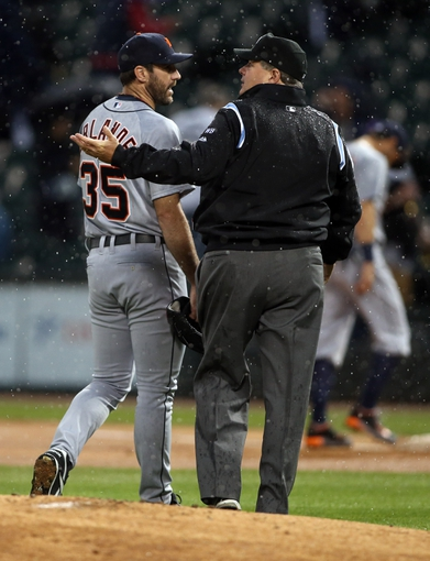 Apr 29, 2014; Chicago, IL, USA; Detroit Tigers starting pitcher Justin Verlander (35) talks with umpire Jerry Layne (24) as rain delays the game against the Chicago White Sox in the first inning at U.S Cellular Field. Mandatory Credit: Jerry Lai-USA TODAY Sports