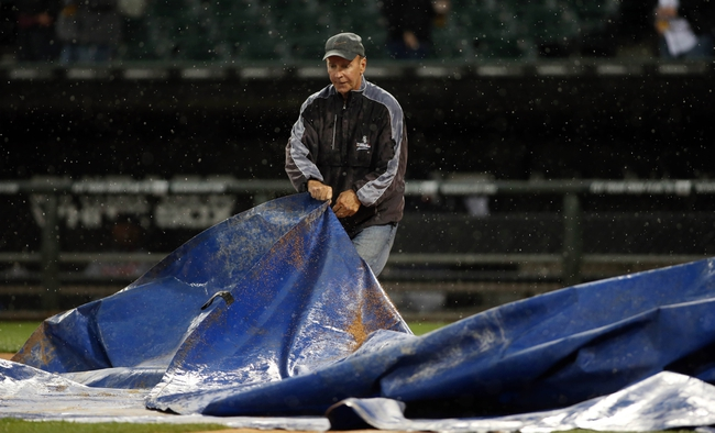 Apr 29, 2014; Chicago, IL, USA; Chicago White Sox head groundskeeper Roger Bossard covers home plate with a tarp as rain delays the game against the Detroit Tigers in the first inning at U.S Cellular Field. Mandatory Credit: Jerry Lai-USA TODAY Sports