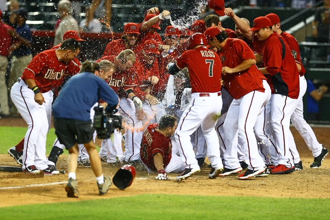 Apr 30, 2014; Phoenix, AZ, USA; Arizona Diamondbacks catcher Miguel Montero slides into home where he is congratulated by teammates after hitting a walk off home run in the tenth inning against the Colorado Rockies at Chase Field. Mandatory Credit: Mark J. Rebilas-USA TODAY Sports