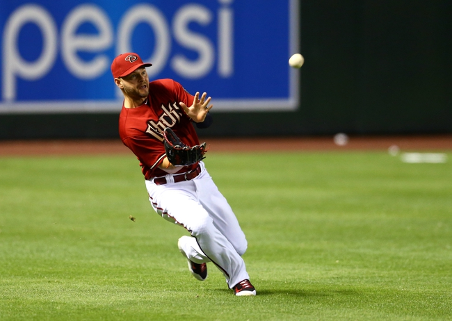 Apr 30, 2014; Phoenix, AZ, USA; Arizona Diamondbacks outfielder Cody Ross attempts to catch a ball in the tenth inning against the Colorado Rockies at Chase Field. Mandatory Credit: Mark J. Rebilas-USA TODAY Sports