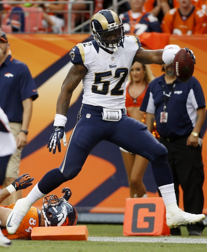 Aug 24, 2013; Denver, CO, USA; St. Louis Rams linebacker Alec Ogletree (52) returns a fumble for a touchdown during the first half against the Denver Broncos at Sports Authority Field at Mile High. Mandatory Credit: Chris Humphreys-USA TODAY Sports