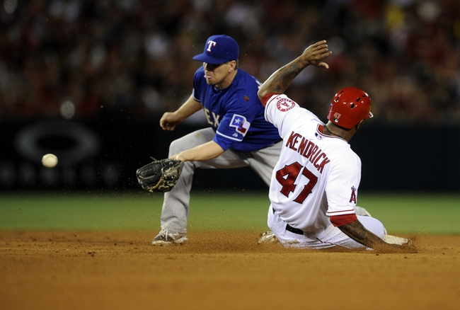 May 2, 2014; Anaheim, CA, USA; Los Angeles Angels second baseman Howie Kendrick (47) slides into second safely off of a steal ahead of the catch by Texas Rangers second baseman Donnie Murphy (16) during the fourth inning at Angel Stadium of Anaheim. Mandatory Credit: Kelvin Kuo-USA TODAY Sports
