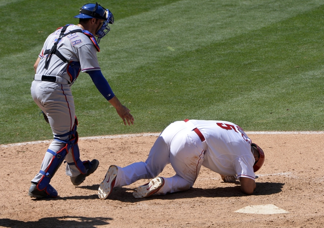 May 4, 2014; Anaheim, CA, USA; Los Angeles Angels first baseman Albert Pujols (5) is on the ground after getting hit in the helmet by a pitch from Texas Rangers starting pitcher Yu Darvish (not pictured) in the 5h inning at Angel Stadium of Anaheim. Left is Texas Rangers catcher J.P. Arencibia (7). Puljos was on the ground for a short time but trotted to 1st base. Mandatory Credit: Robert Hanashiro-USA TODAY Sports