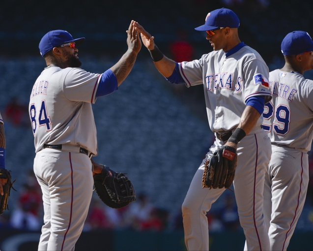 May 4, 2014; Anaheim, CA, USA; Texas Rangers first baseman Prince Fielder (84) high-fives teammate right fielder Alex Rios (51) at the end of the Rangers 14-3 win over the Los Angeles Angels at Angel Stadium of Anaheim. Mandatory Credit: Robert Hanashiro-USA TODAY Sports