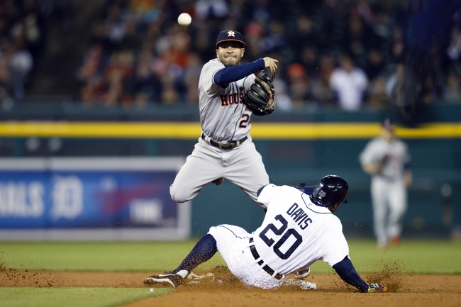 May 5, 2014; Detroit, MI, USA; Houston Astros second baseman Jose Altuve (27) makes a throw to first to complete a double play as Detroit Tigers left fielder Rajai Davis (20) slides into second base in the seventh inning at Comerica Park. Mandatory Credit: Rick Osentoski-USA TODAY Sports